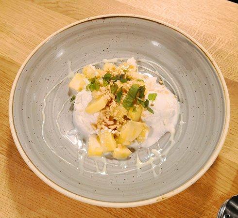 Mangowürfel an hausgemachtem veganen Bio-Kokosnuss-Eis nach thailändischer Rezeptur mit Topping aus gerösteten Erdnüssen.
