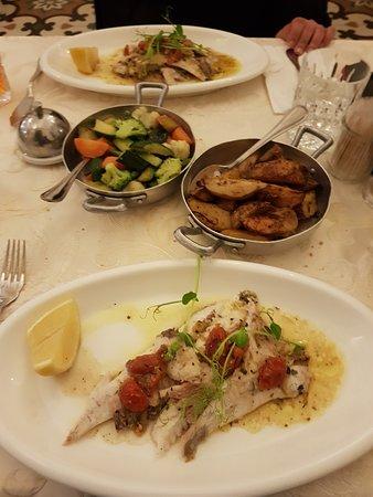 Pesce San Pietro plated accompanied with roast potatoes and mixed veg