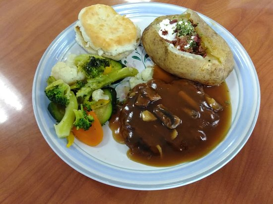Roundup, MT: Salisbury Steak Dinner with Baked Potato, vegetables and a biscuit.
