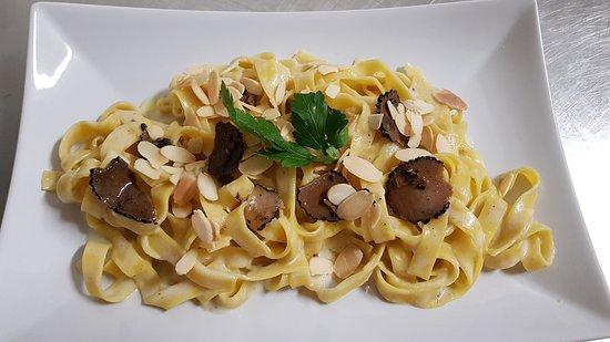 tagliatelle fresche di pasta all'uovo con salsa al tartufo e lamelle di mandorle tostate
