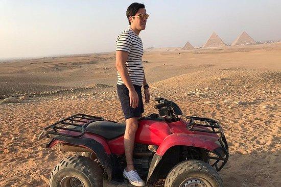 ギザのピラミッドの門のまわりでのラクダ乗りとクワッドバイク
