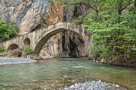 The amazing Portitsa Canyon, having an old stone bridge at its entrance. Ready to explore this magnificent scenery?  #greek_adventure #greece #portitsa #canyoning #hiking #grevena #experiencedifferentgreece #holidaysingreece
