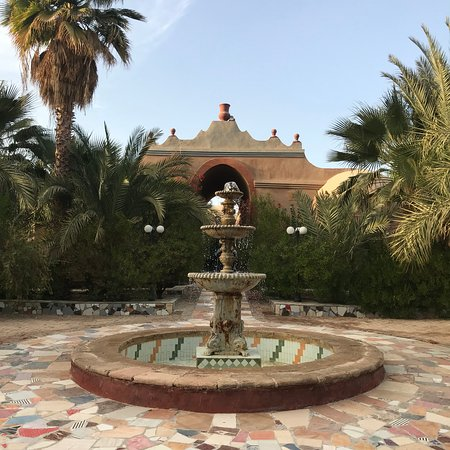 Al Moudira Hotel : Tile walking paths between buildings are filled with plants and fountains.