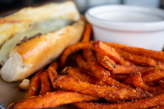 French Dip sandwich made with shaved ribeye and topped with Swiss cheese. Served with sweet potato fries, and house made au jus for dipping.