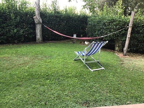 Agriturismo Dolce Verde: Hamac et chaises longues devant l'appartement.