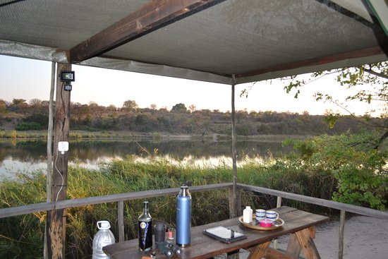 Rundu, Namibia: Frühmorgens bringt der Chef eine Thermoskanne Kaffee mit Tassen, Milch und Zucker auf die Terrasse.