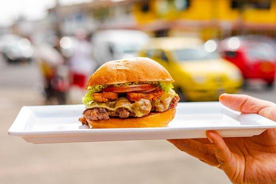 """Hamburguesas Pecado Capital - Normandia: Sabores colombianos concentrados en esta hamburguesa que le dará """"Envidia"""" a la competencia. Tajadas de longaniza sobre un queso Paipa derretido encima de una carne jugosa y nuestro pan de papa."""