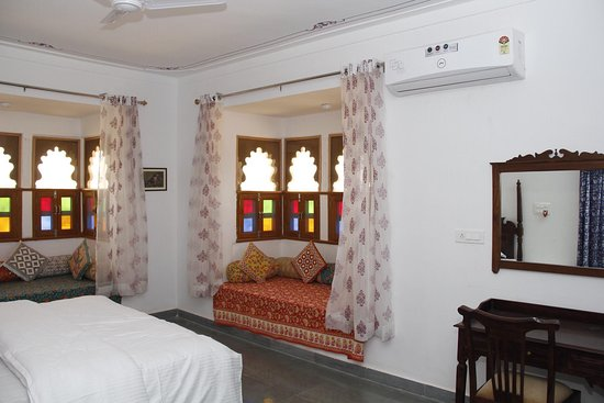 Fully furnished rooms with Kota stone polished flooring with traditional Rajasthani jarokhas with Bombay Dyeing linen & quilts on bed and block prints linen in jarokhas.