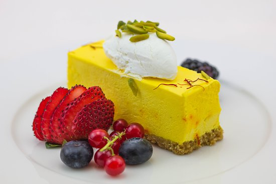 Saffron Cheesecake - The signature of Mitts and Trays. Saffron infused heavy cream cheesecake with soft pista crumble, cream quenelle, and berries.