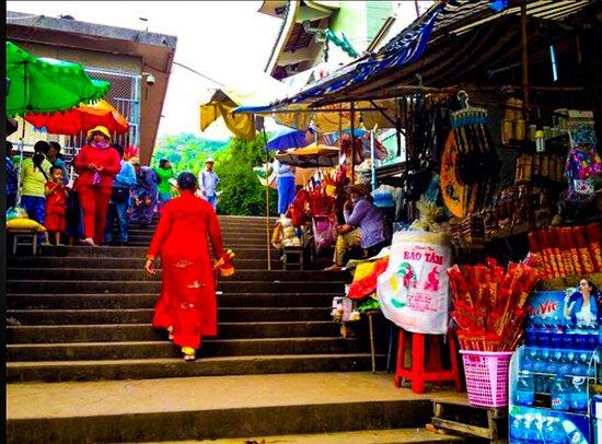 Mekong Delta, Vietnam: Pilgrims make their way up past stalls to the mountain