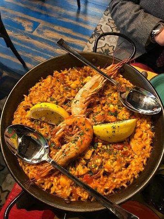 Paella con pezzetti di salsiccia, pollo, pesce, calamari, e decorata con due gamberoni