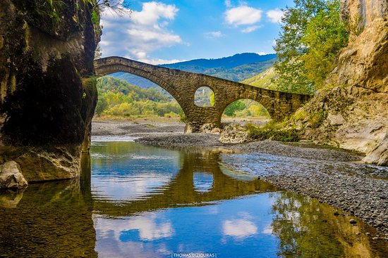 The magnificent Portitsa gorge with the old stone bridge at its entrance. Located close to Spilaio village in Grevena. The spot is generally accessible by car (dirt road for about 5km) or by hiking the beautiful path from the village.