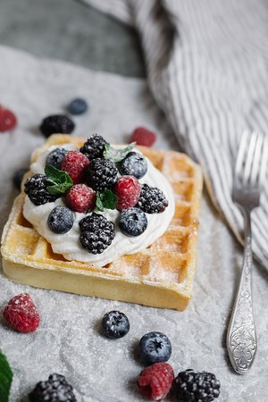 Belgian waffle with sweet topping and berries