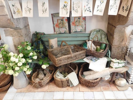 Dinan, France: Anciennes planches lithographiées de fleurs, vieux paniers en osier, toiles à torchons en métis, pots de fleurs vernissés...
