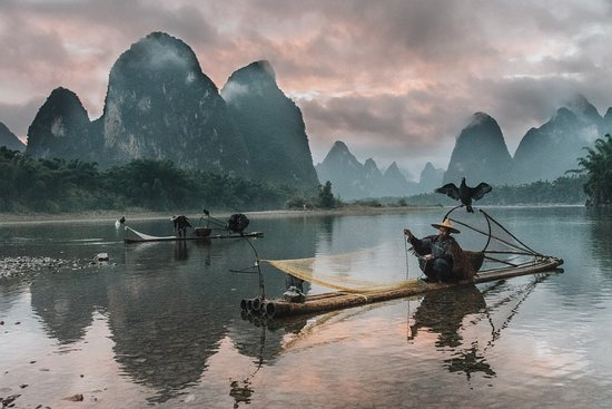 Li County, China: Sunset on the Li River in China, as the few remaining cormorant fisherman pack their nets for the night.  Credits: Sam Beasley