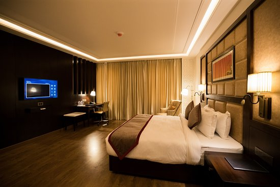 Suite Room: One room with spacious bedroom & living room furnished with sofa seating and dining