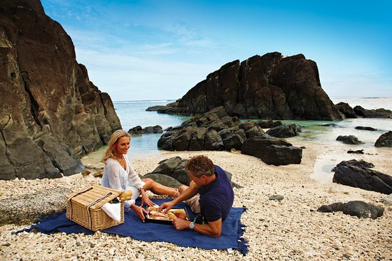 Isole Cook: A quite lunch for two whilst enjoying the view. A stunning setting at the famous black rock beach located in Nikao, Rarotonga.