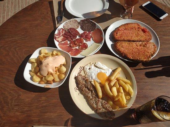 Monells, Spain: Patatas bravas, butifarra con huevo frito y plato de chacinas.