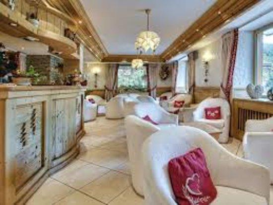 Salon et bar de l'hôtel à l'ambiance cosy avec cheminée ouverte et vue sur le village et la chaîne des Aravis.