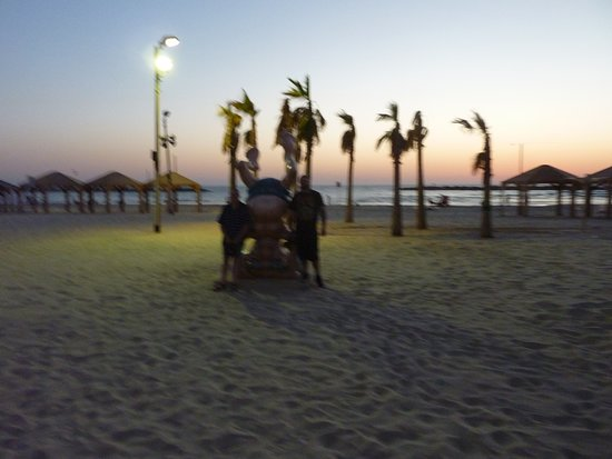 """Tel Aviv, Israel: At dusk with my son, near Ben Gurion's image of """"Standing on your head""""."""