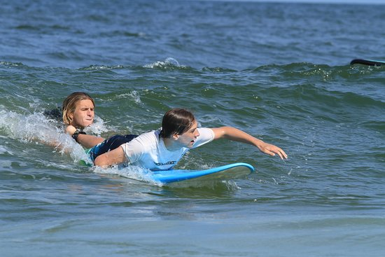 Hatteras Island Surf and Sail: Reider on a surf lesson sending a student in to pop up!
