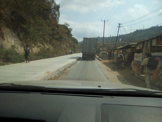 Bas-Congo Province, สาธารณรัฐประชาธิปไตยคองโก: Nationale numéro 1, Ville de Matadi. On voit à notre gauche la couche de béton qui va devenir la nouvelle voie et la piste que nous suivons est l'ancienne voie qui à son tour recevra du béton afin que le niveau de la chaussée soit le même.