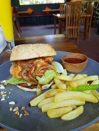 Chicken burger with caramelized onions, fries, and Mango juice