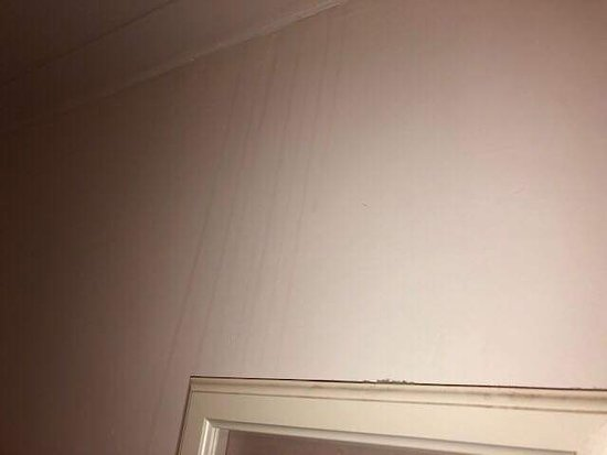 Picture above bed covered in loads of dust, with stain on the wall...