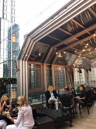 Rooftop bar with sliding glass roof that can close when cold or wet.