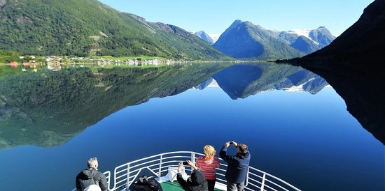 Balestrand, Norge: Approaching Fjærland with calm fjord and glacier in back ground.