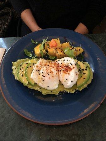 Torradas com abacate, ovo e uma salada de manga.