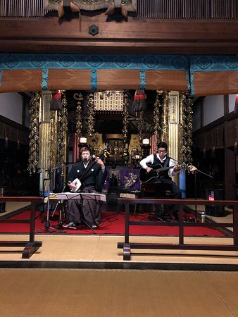 shamisen and guitar duo in front of Buddha