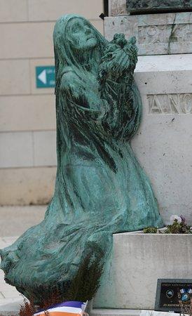 Saint-Amour, França: Dans la douleur, à  genoux, je pleure mon mari mais à mes pieds, on a mis un pot de fleurs fanées. De plus à 50 cm, de moi,  il y a un cœur pour célébrer la fête des amoureux ! Comment puis-je interpréter cette situation, alors que je suis devant la mairie et l'office de tourisme ? Que dire ! Pauvre France ! Que fais-tu de tes morts !