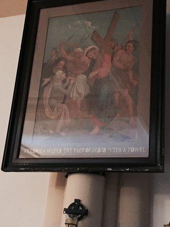 Parroquia San Patricio: Leyendas en inglés debajo de las pinturas de la pasión de Cristo.