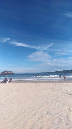 Praia tranquila com mar mais agitado.