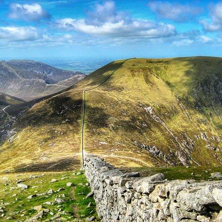 County Down, UK: Las montañas de Mourne en Irlanda del Norte ofrecen rutas preciosas con antiguos muros que se encaraman a las laderas y vistas al océano.
