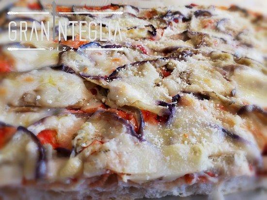 Graninteglia : Sull onda del gusto e della leggerezza, ecco un'altra proposta sfiziosa: la nostra parmigiana! Pizza rossa con fettine di melanzane fini cotte al forno, scamorza e parmigiano. Un gusto davvero davvero piacevole... Una delle mie preferite!
