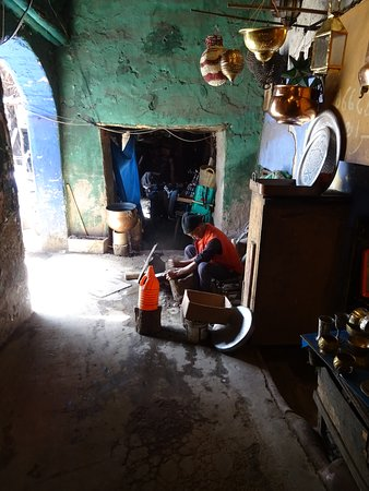 à côté, un artisan travaille le cuivre et le métal