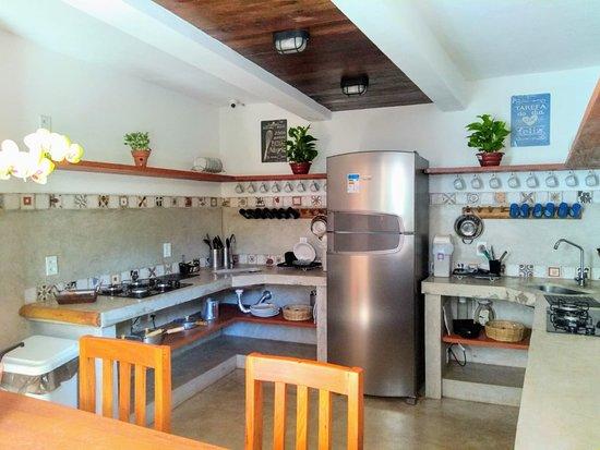 Cozinha com 2 fogões Cooktop, 2 pias, geladeira de inox e bancadas. Toda equipada com utensílios, incluindo microondas e liquidificador