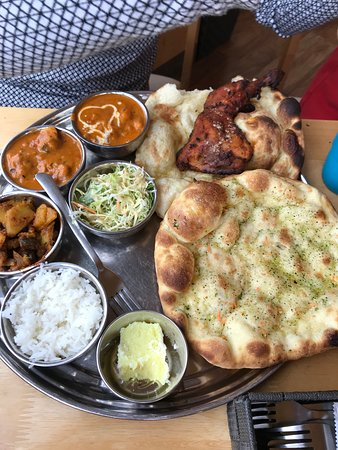 Lunch plate with three curries, vegetables, rice, tandoori chicken and garlic naan!