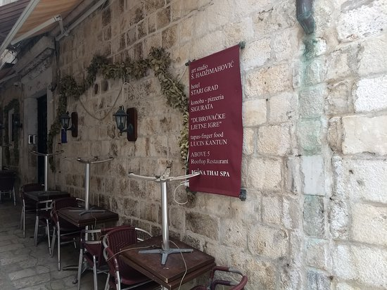 """This photo shows you how to access Dubrovnik's Lucin Kantun restaurant.  As you walk from the main entry into Dubrovnik's Old City, you'll walk down a broad plaza heading to the wharf.  This alley will be on your left, about 100-meters down.  The fabric hanging banner lists the name of all of the restaurants located here.  Look for """"Lucin Kantun"""" on the banner.  (couldn't find out how to attach photo to existing review)"""
