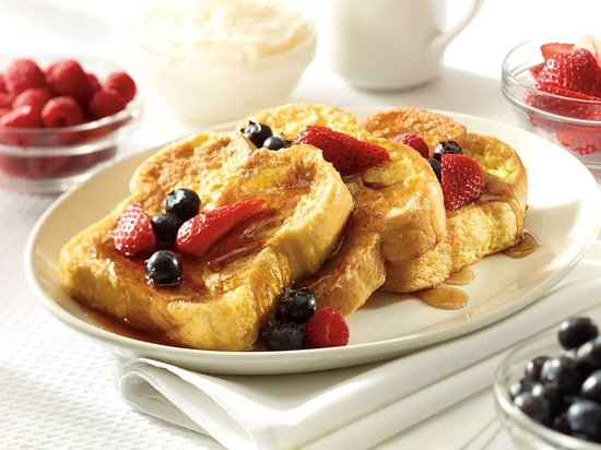 Three slices of thick French toast topped with pure maple syrup and fresh fruit.