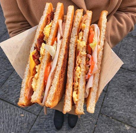 CLUB TOAST Toast a due piani farcito con bacon, formaggio cheddar, uova strapazzate, tacchino, insalata, pomodori, maionese.