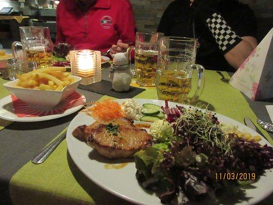 St. Niklaus, Switzerland: Fitnessteller mit Schweinerückensteak und Kräuterbutter. Dazu Pommes bei einem leckeren Bier aus dem Fass.