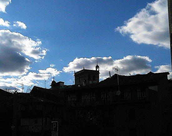 Vista de casas con la Torre de la Iglesia (con la torrecilla campanera) al fondo.