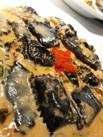 ravioles negros de salmon y un pequeño detalle de caviar rojo