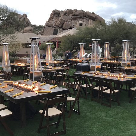 Outside event with fire tables near boulder pile