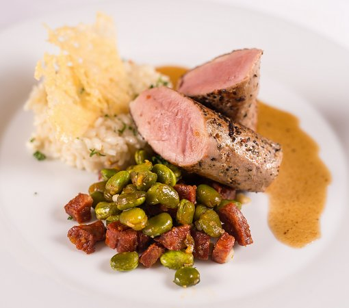 Pink roasted pork fillet (200g), risotto with chorizo, fava beans and parmesan chips