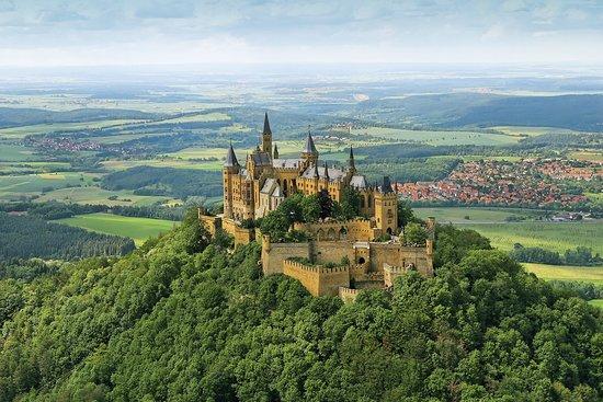 """Hechingen, เยอรมนี: Die Burg Hohenzollern ist der Stammsitz der Preußischen Könige, Deutschen Kaiser und Fürsten von Hohenzollern. Die beeindruckende Burganlage wurde im 19. Jahrhundert wiederhergestellt und befindet sich bis heute im Familienbesitz. Nicht zuletzt ist es auch die einzigartige Lage, die bereits Kaiser Wilhelm II. zu dem Ausspruch animierte, dass der """"Ausblick von der Burg Hohenzollern wahrlich eine Reise wert ist""""."""