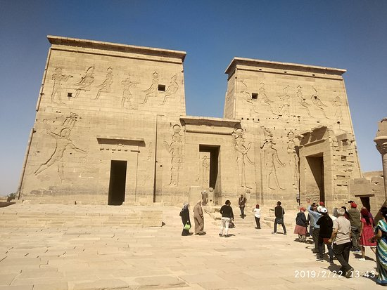 Philae Tapınağı: Magnificent 18 meters high first gates of Temple of Isis at Philae. To giant lion statues placed on bith sides of the gate. hieroglyphic on extreme showRamses beheading an enemy.